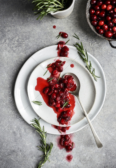 A rustic homemade cranberry sauce spooned across a stack of plates with fresh rosemary and cranberries throughout the frame