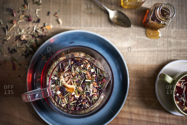 Beautiful tray of tea being prepared. Overhead showing texture of loose leaf tea floating in glass teapot with honey jars, spoon and mug