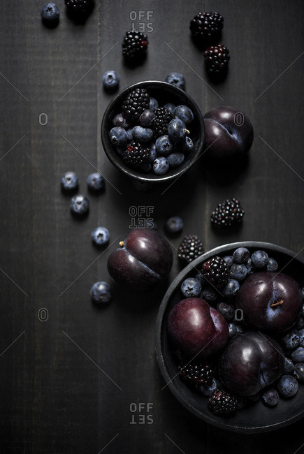 Bowls of blue and black fruits laid out artistically and beautifully on a dark wood surface. Dark and moody