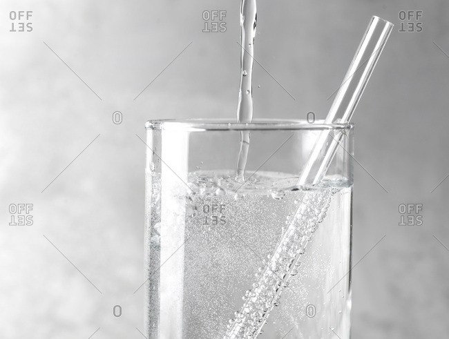 Detail of sparkling water being poured into a clear glass with a clear straw on a gray metal background