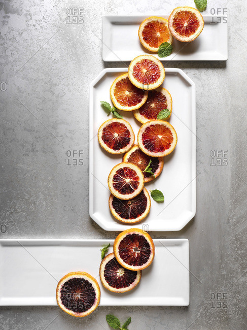 Blood orange slices layed out in artistic shape over white plates and textured metal surface