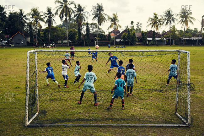 Bali, Indonesia - January 6, 2017: Kids playing soccer in field