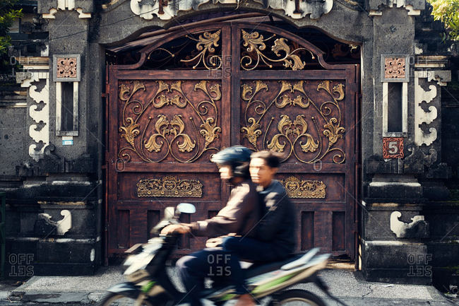 Bali, Indonesia - January 9, 2017: Two young men on a motorbike by ornate gate