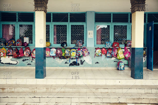 Bali, Indonesia - January 24, 2017: Backpacks hanging on the exterior wall of a school