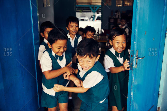 Bali, Indonesia - January 24, 2017: School kids laughing in doorway