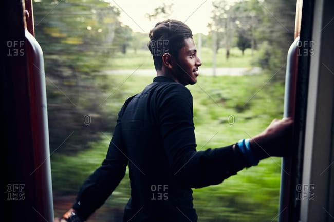 Colombo, Sri Lanka - January 31, 2017: Young man in train doorway