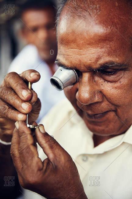 Anuradhapura, Sri Lanka - February 2, 2017: Jeweler using magnifying tool