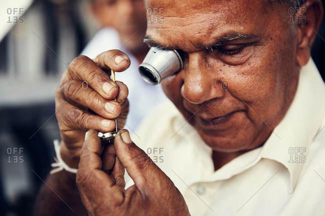 Anuradhapura, Sri Lanka - February 2, 2017: Man using a magnifying tool