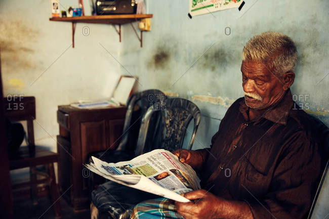 Jaffna, Sri Lanka - February 3, 2017: Old man reading newspaper in home
