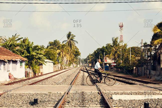 Jaffna, Sri Lanka - February 3, 2017: Man crossing train tracks on bike