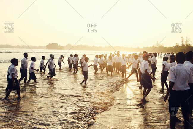 Weligama, Sri Lanka - February 17, 2017: Schoolboys gathered on a beach
