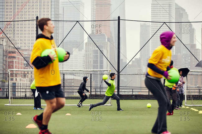 New York City - May 13, 2017: People playing dodge ball in rain