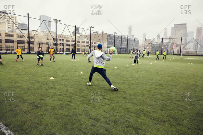 New York City - May 13, 2017: Adults playing dodge ball in the rain