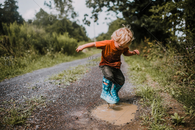 Boy jumping in boots in puddle