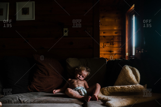 Toddler boy asleep sitting on couch
