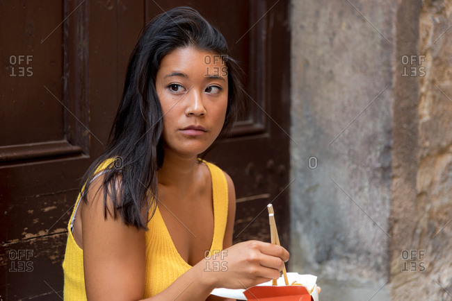 Young asiatic woman eating a chinese take-away on her doorstep