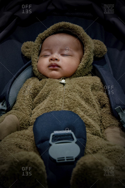 High angle view of toddler in bear suit sleeping in car