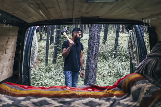 Man looking away while holding axe in forest seen through vehicle
