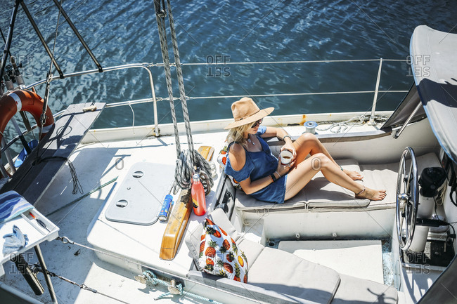 High angle view of woman relaxing in sailboat on sea