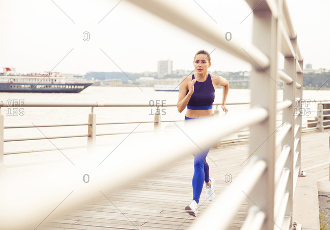 Woman running while exercising on bridge in city