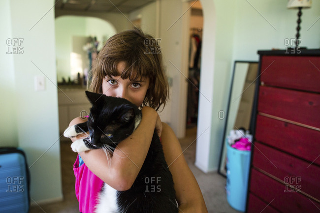 Portrait of girl carrying cat at home