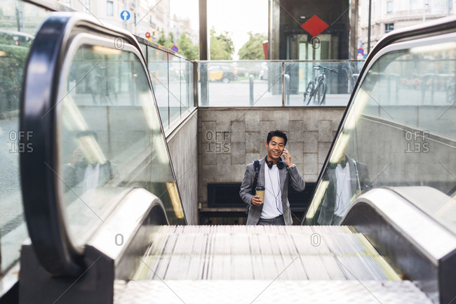 Businessman talking on smart phone while standing on escalator