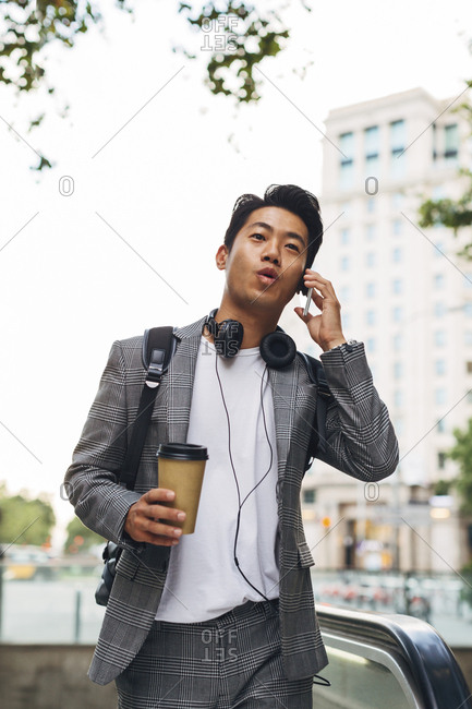 Businessman talking on smart phone while holding disposable cup in city