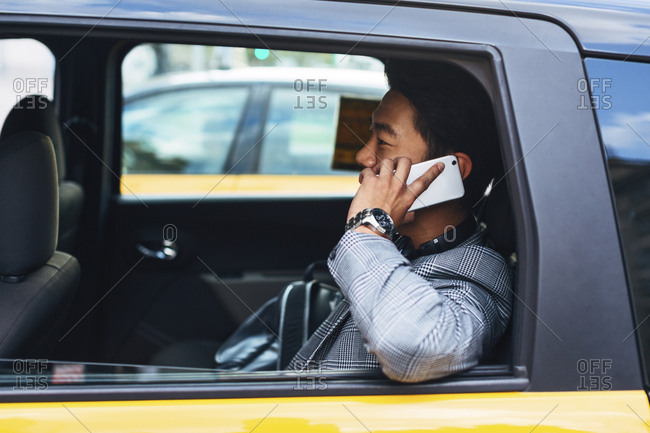 Businessman talking on smart phone while sitting in taxi