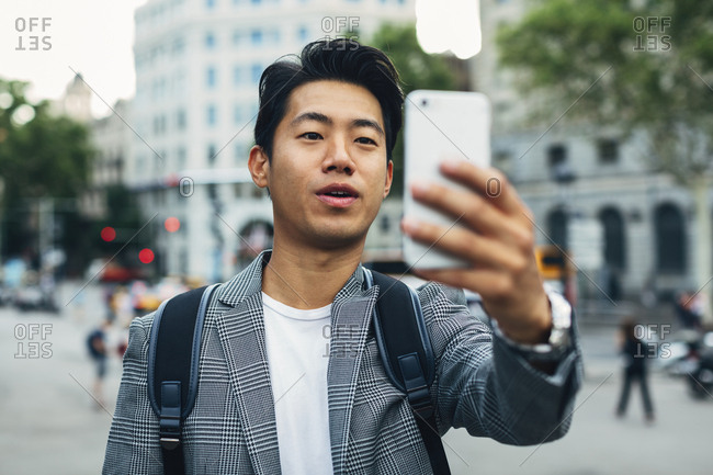 Businessman with backpack taking selfie through smart phone while standing on footpath