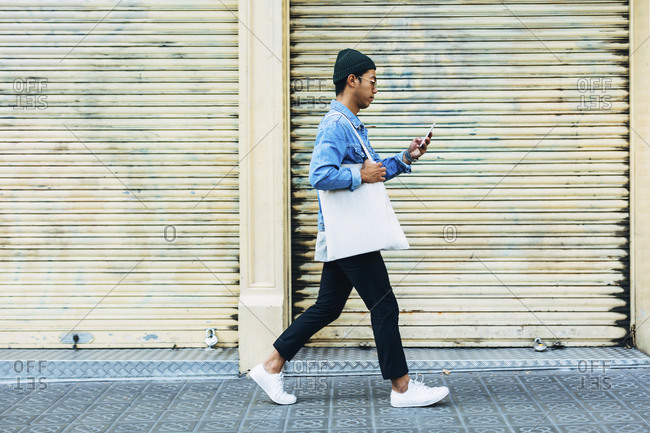 Man using smart phone while walking against shutter