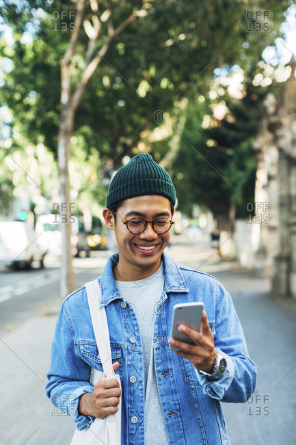 Happy man using smart phone while standing at sidewalk