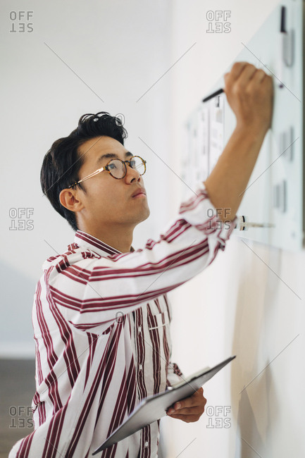 Serious businessman holding clipboard while writing on whiteboard in office