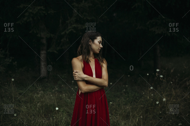 Woman hugging self while standing on grassy field