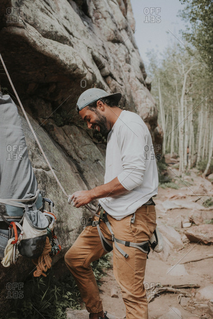 Happy man tying rope before mountain climbing