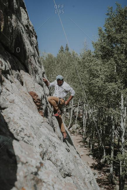Man looking down while mountain climbing