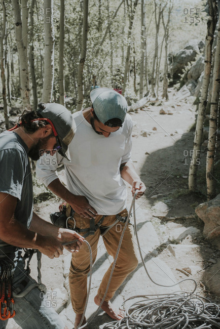 High angle view of friends preparing for mountain climbing