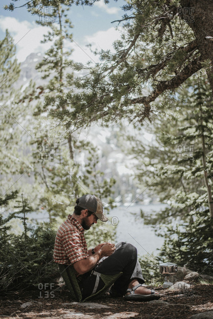 Side view of hiker sitting in camping seat at forest