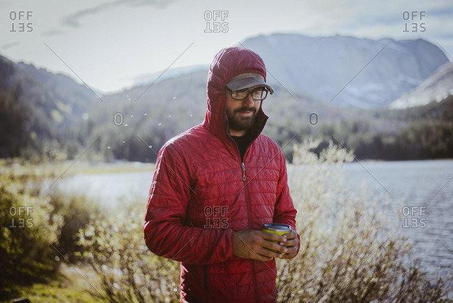 Hiker in hood holding drink can while standing by lake at Grand Teton National Park