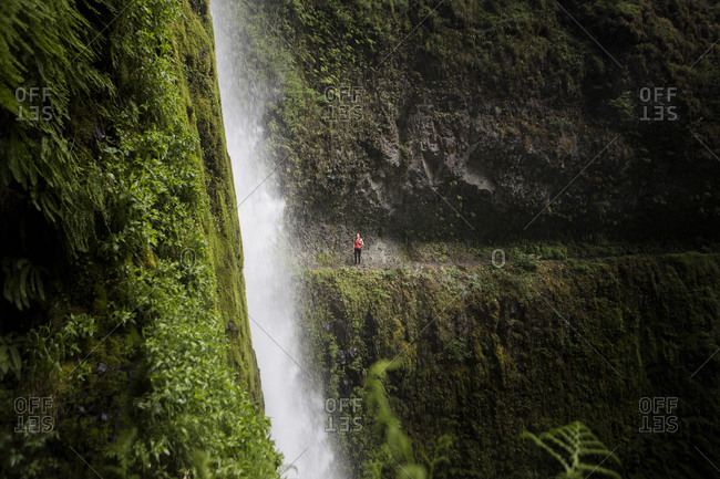 Distant view of female hiker standing at Eagle Creek Trail with Tunnel Falls in foreground