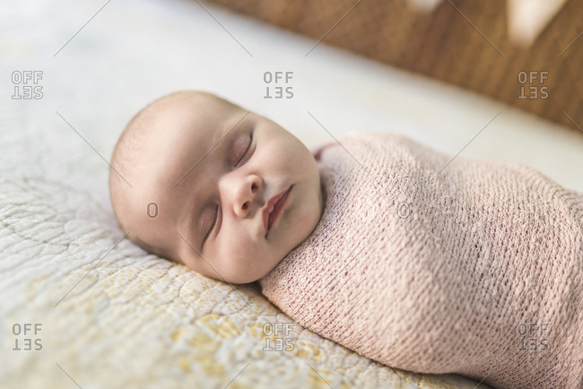 Close-up of baby girl sleeping while wrapped in blanket on bed