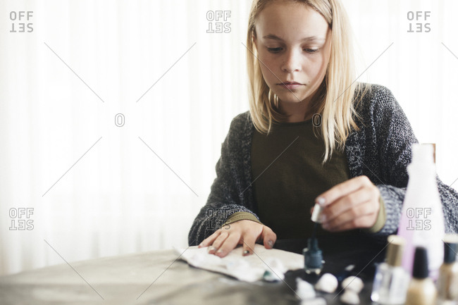 Girl painting fingernails on table at home