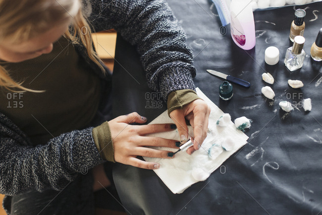 High angle view of girl painting fingernails on table at home