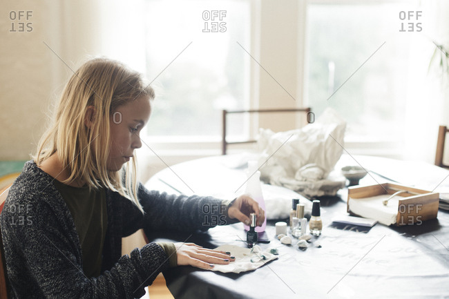 Girl painting fingernails on table while sitting against window
