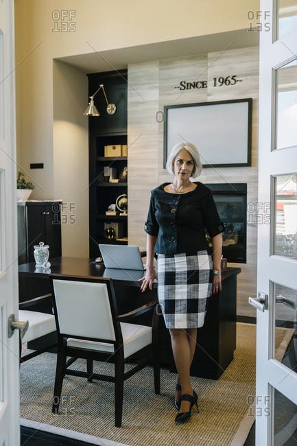 Full length portrait of confident businesswoman in office seen through doorway
