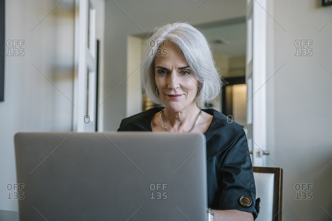 Serious businesswoman working on laptop computer in office