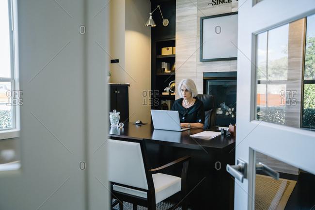 Businesswoman working on laptop computer at desk in office seen through doorway