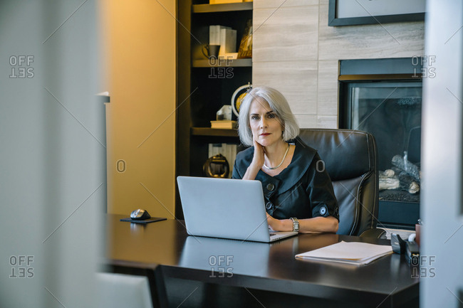 Portrait of businesswoman working on laptop computer at desk in office seen through doorway