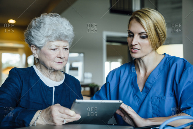Home caregiver assisting senior woman in using tablet computer
