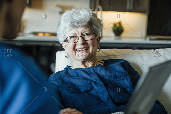 Happy senior woman looking at home caregiver in living room