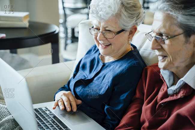 Senior couple using laptop computer in living room